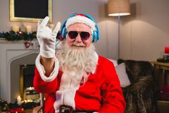 Santa claus listening to music on headphones at home. Smiling santa claus listening to music on headphones at home Royalty Free Stock Photo