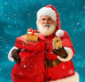 Smiling Santa Claus with new year presents and looking at camera Stock Photos