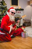 Smiling santa claus playing a guitar Stock Photo