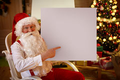 Smiling Santa Claus pointing in empty banner. While sitting in his living room stock photos