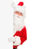 Smiling Santa Claus posing behind a blank panel. Isolated on white background Stock Photos