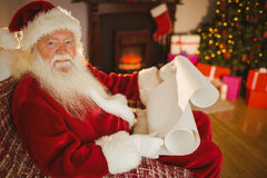 Smiling santa claus reading his list Stock Photography