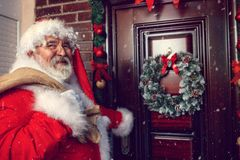 Santa Claus with sack in front of Christmas door Royalty Free Stock Photo