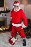 Smiling santa claus standing with a guitar Stock Photos