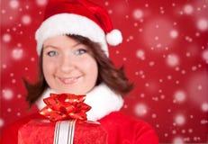 Smiling santa girl holding a big red gift Royalty Free Stock Image