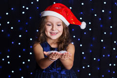 Smiling santa girl is looking at snow in hands Stock Image