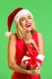 Smiling santa girl opening a gift Stock Photos