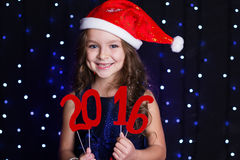 Smiling santa girl with red new year date 2016 Stock Image