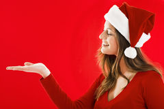 Smiling Santa Girl showing. Smiling Santa Girl presenting your product, lots of copy-space Royalty Free Stock Photos