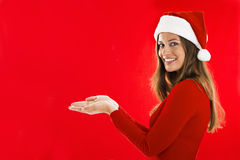 Smiling Santa Girl showing. Smiling Santa Girl presenting your product, lots of copy-space Stock Photography