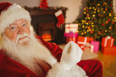 Smiling santa holding engagement ring Royalty Free Stock Photos