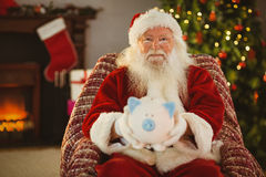Smiling santa offering piggy bank Royalty Free Stock Photo