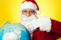 Smiling santa pointing at globe map. stock photography