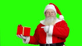 Smiling santa`s holding the present and pointing at it. stock footage