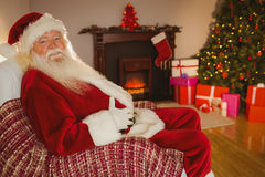 Smiling santa sitting and holding his belly Stock Photography