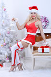 Smiling santa woman near the Christmas tree Royalty Free Stock Photos