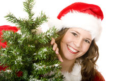 Smiling Santa Woman standing near Christmas tree. Young woman dressed as Santa Claus is standing beside a Christmas tree and smiles happy. Isolated on white Stock Photo