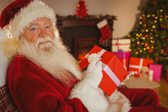 Smiling santa writing on a red gift Royalty Free Stock Photos