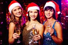 Smiling Santas. Three cheerful girls in Santa caps wishing you merry Christmas royalty free stock images