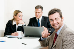 Smiling satisfied businessman. Looking at camera with his colleagues in the background during a meeting in the office Stock Images