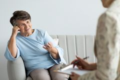 Smiling satisfied senior woman talking to a psychotherapist stock photo