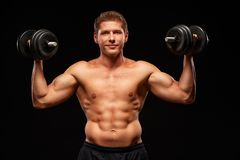 Smiling satisfied sportsman with dumbbells in hands, isolated on black. Smiling powerful shirtless muscular sportsman pumping biceps muscles with black dumbbells Royalty Free Stock Photo