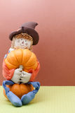 Smiling Scarecrow Holds A Pumpkin While Seated Stock Photo