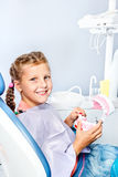 Girl cleaning toy dentures Stock Images