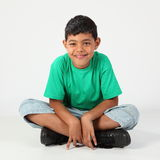 Smiling school boy 9 sitting cross legged on floor. Close up portrait of happy young ethnic school boy, 9, wearing green t-shirt sitting cross-legged on studio Royalty Free Stock Photo