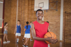 Smiling school boy holding a basketball while team playing in background. Portrait of smiling school boy holding a basketball while team playing in background Royalty Free Stock Image