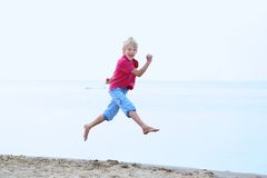 Smiling school boy jumping on the beach. Happy kid, active teenager boy, having fun on the beach on a sunny summer day jumping high on the shoreline Stock Photos