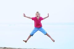 Smiling school boy jumping on the beach. Happy kid, active teenager boy, having fun on the beach on a sunny summer day jumping high on the shoreline Royalty Free Stock Photo