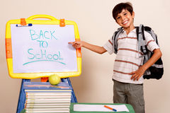 Smiling school boy pointing at white board Royalty Free Stock Images