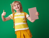 Smiling school girl with book showing thumbs up Stock Image