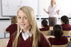 Smiling school girl in classroom with students and teacher royalty free stock photo
