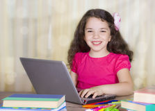 Smiling school girl with laptop at desk Stock Photo