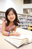 Smiling School Girl Reading Book at Library Stock Image