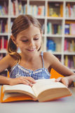 Smiling school girl reading a book in library royalty free stock photo