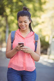 Smiling school girl with schoolbag using mobile phone in campus Stock Photos