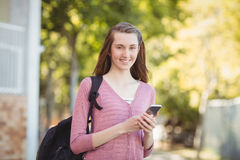 Smiling school girl with schoolbag using mobile phone in campus Royalty Free Stock Photos