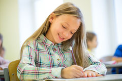 Smiling school girl writing test in classroom Royalty Free Stock Photo