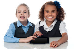 Smiling school girls playing on touchpad Stock Photography