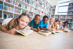 Smiling school kids lying on floor reading book in library Stock Images