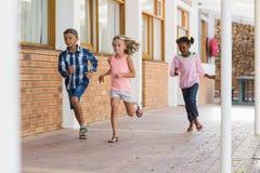 Smiling school kids running in corridor Stock Photo