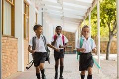 Smiling school kids running in corridor Royalty Free Stock Photo