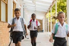 Smiling school kids running in corridor Royalty Free Stock Images