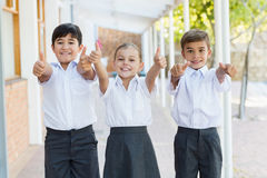 Smiling school kids showing thumbs up in corridor. Portrait of smiling school kids showing thumbs up in corridor at school Stock Images