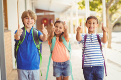 Smiling school kids showing thumbs up in school corridor. Portrait of smiling school kids showing thumbs up in school corridor Royalty Free Stock Photography