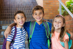 Smiling school kids standing with arm around royalty free stock image