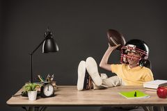 smiling schoolboy in american football helmet holding ball and sitting with legs on table with books plant lamp colour